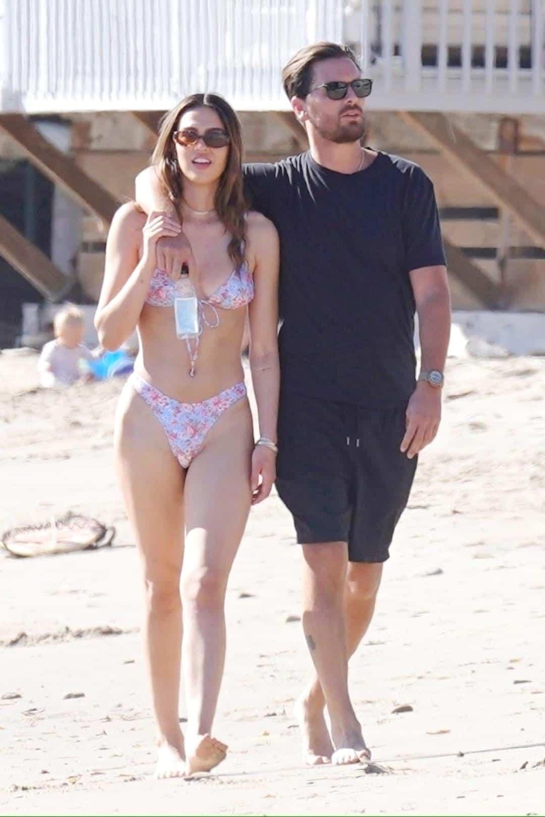 Amelia Hamlin and Scott Disick walking on the beach with Scott's arms around Amelia